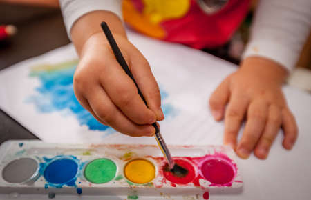 Little girl painting watercolors with her hands photo