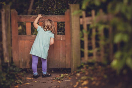Young girl peeking through the hole in the small wooden gates in the garden Stock Photo