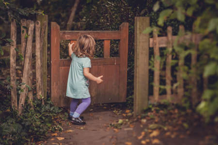 Young girl closing the wooden gates in the garden photo