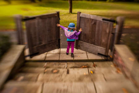 niño empujando: Chica joven que abre las puertas de madera en el jardín