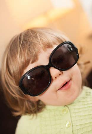 designer baby: Portrait of a cute little baby girl wearing large dark designer glasses