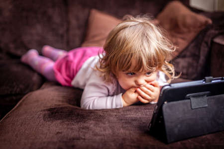 babygirl: Little girl laying on a sofa and watching cartoon on a small tablet Stock Photo