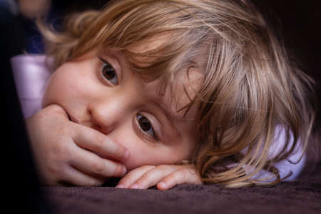 Little girl laying on a sofa and watching cartoon on a small tablet photo