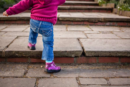 Cute baby girl climbing up the wide stairs in the park Standard-Bild