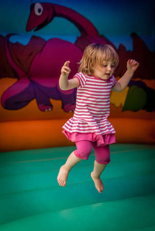 Cute little girl jumping inside the inflatable bouncy