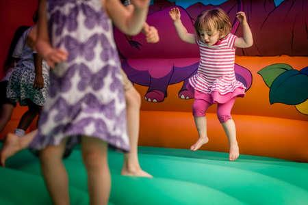 Schattig klein meisje springen in het opblaasbaar springkasteel Stockfoto