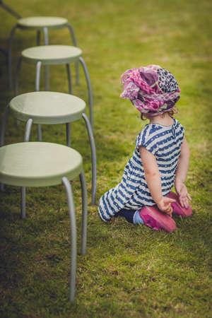 cabizbajo: Retrato de una ni�a enojado y molesto que se sienta en la hierba al lado de una silla