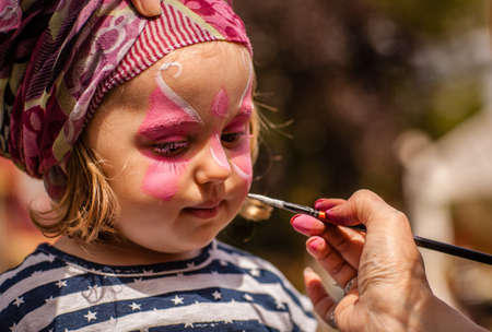 fair skin: Little girl having her face painted during local fair