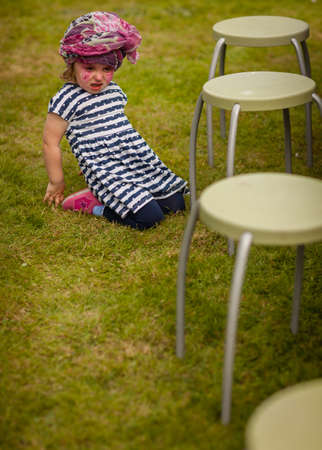 teary: Portrait of an angry and upset little girl sitting on the grass next to a chair Stock Photo