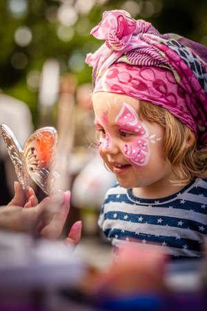 Klein meisje met haar gezicht geschilderd tijdens plaatselijke kermis Stockfoto