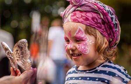 Kleines Mädchen, das ihr Gesicht während lokale Messe gemalt Standard-Bild - 33801962