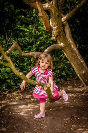 Cute little girl jumping over branches of a small tree in the park in spring photo
