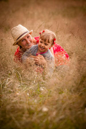 Portrait of a happy family - mother and daughter posing on a meadow photo