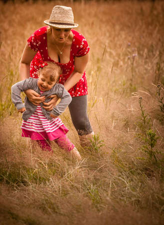 Mother and daughter playing together on a meadow photo
