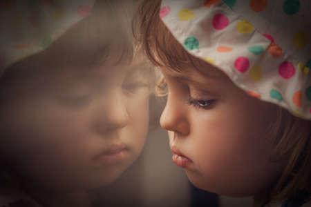 Venster weerspiegeling van een beetje verdrietig meisje