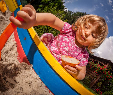 Girl playing in the sandpit in the home garden photo