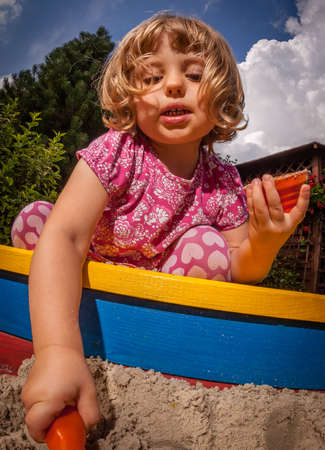 sandpit: Girl playing in the sandpit in the home garden Stock Photo