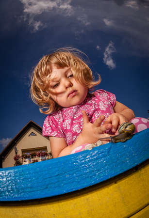 Little girl looking at the snail creeping on top of the sandpit photo