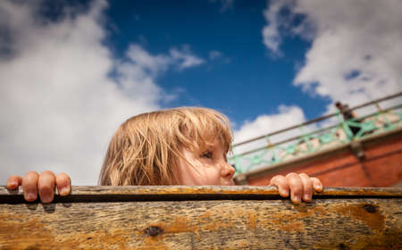 seaside town: Little girl looking out from a boat in seaside town Brighton in UK