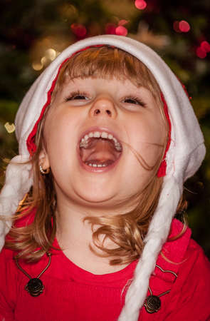 mesmerized: Cute Christmas girl with the Christmas tree in the background Stock Photo
