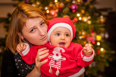 Portrait of a happy mother and her baby boy in front of the Christmas tree photo