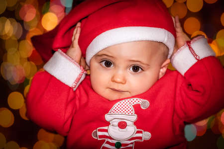9 months old: Little 9 months old boy dressed in Christmas outfit with a backround bokeh of Christmas tree lights