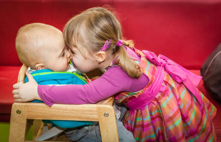 Little girl giving hugs and kisses to her little brother sitting in a wooden high chair photo