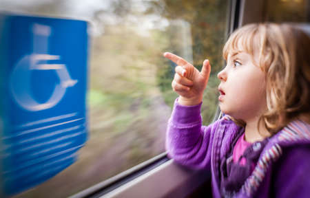freetime: Little girl sitting inside the train carriage and pointing outside