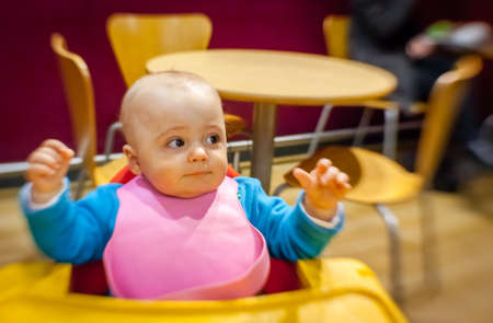highchair: Little boy sitting in a highchair in a cafe inside a shopping mall