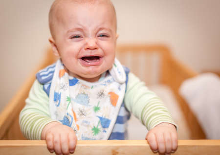 Little boy, infant, standing in his bed and crying loudly photo