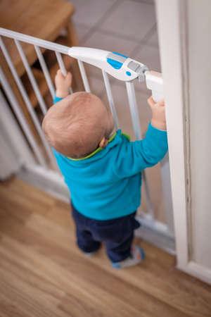 caja fuerte: Niño de pie detrás de las puertas que no le permitan entrar en la cocina