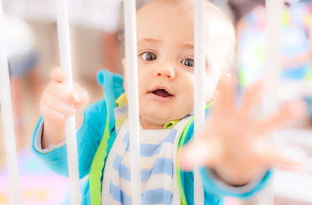 Little boy standing behind the gates preventing him from entering the kitchen photo