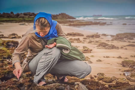 Woman collecting shells on the beach in Queshm, Iran photo