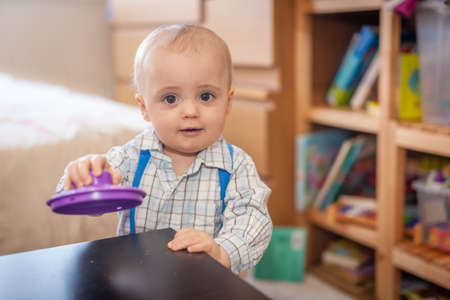 Portrait of a cute little baby boy playing with toy at home photo
