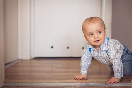 Portrait of a adorable baby boy crawling on the floor at home photo
