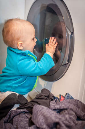 Portrait of a cute little baby boy looking with fascination inside the washing machine photo