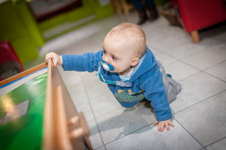 Portrait of a adorable baby boy crawling on the floor at nursery photo