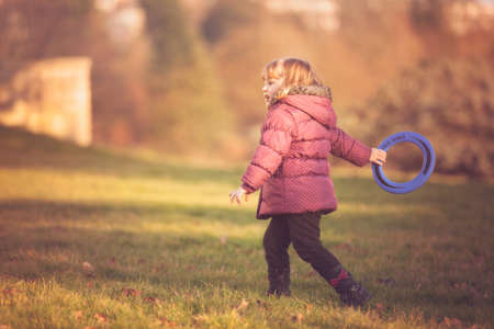 flying disc: Little girl throwing flying disc in the park in autumn