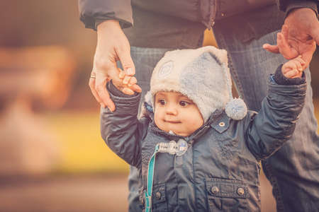 Little boy learning to walk with his mother in a park in early autumn photo