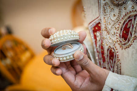 Indian groom holding box containing wedding rings