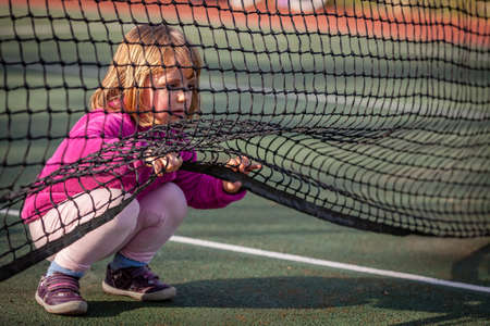 crawling: Little girl crawling under the net on the tennis court