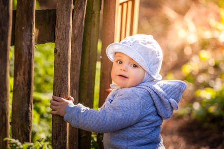 shutting: Young boy opening the wooden gates in the garden Stock Photo