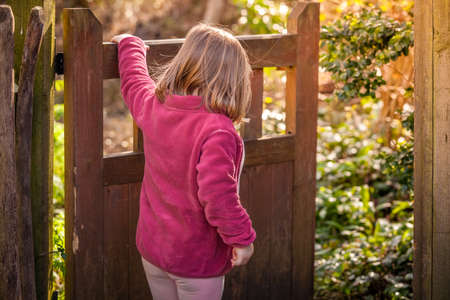 Young girl opening the wooden gates in the garden Stock Photo