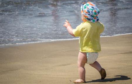 shoeless: Little boy running towards the sea on holiday Stock Photo