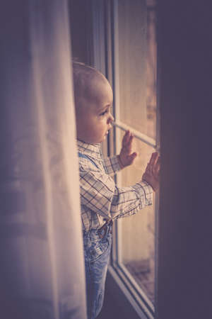 balcony window: Portrait of a cute little baby boy standing and looking through the balcony door window