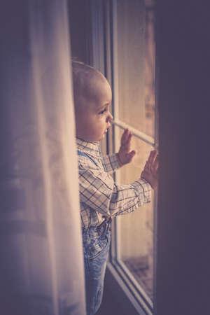 balcony door: Portrait of a cute little baby boy standing and looking through the balcony door window