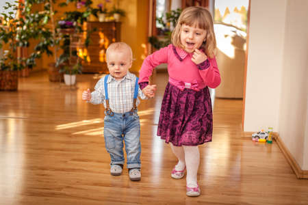 Little kids  brother and sister playing together in the living room at home