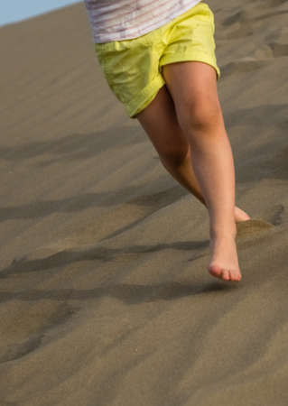 canarian: Little girl running down the sand dunes in  the Natural Reserve of Dunes of Maspalomas in Gran Canaria