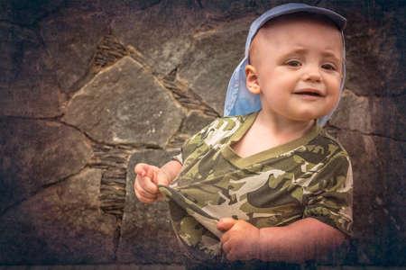mischevious: Portrait of a happy little boy holding his tshirt