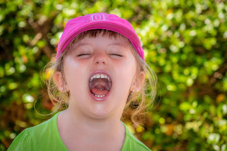 loudly: Little girl standing in a park and shouting loudly